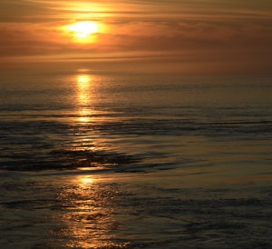 As the tide ebbs, the sun sets through the fog reflected in the boils and rips.