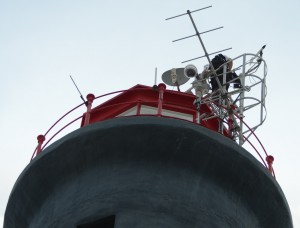 Environment Canada crew service their weather station atop the Race Rocks Light tower, with full safety gear.